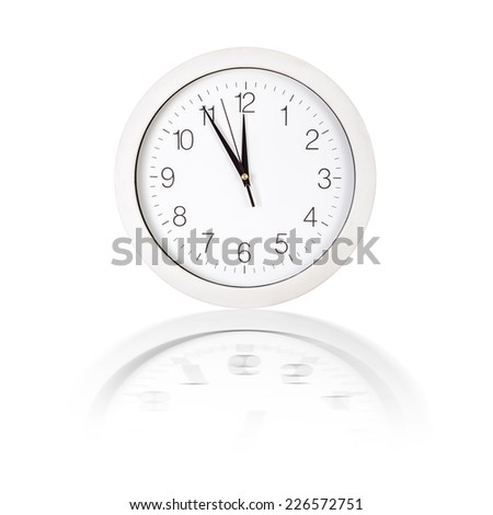 Clock face showing five minutes to twelve on white background - stock photo