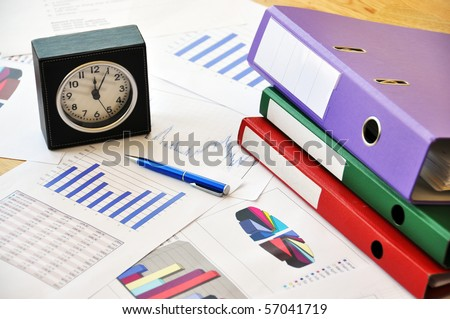 Clock, files and pen on a market report - stock photo