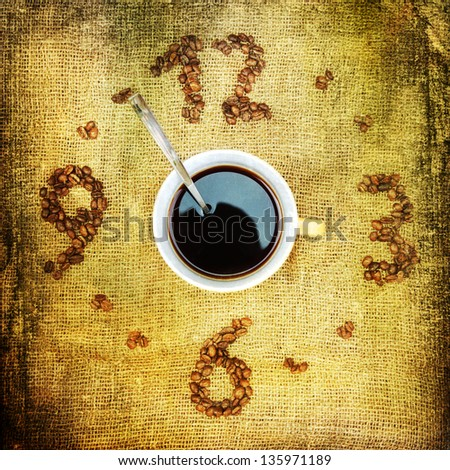 clock from coffee beans on burlap with a cup of coffee in the middle showing the time