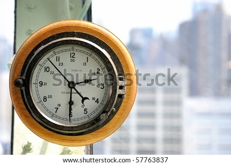 Clock in steering room of aircraft carrier with New York City in background.