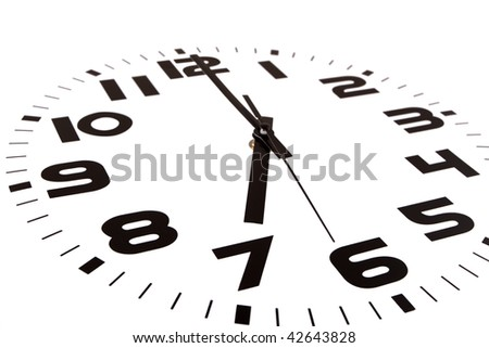 Clock isolated on white marking the seven o'clock hour. The main focus is in the hour hand. - stock photo