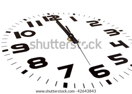 Clock isolated on white marking the twelve o'clock hour. The main focus is in the hour hand. - stock photo