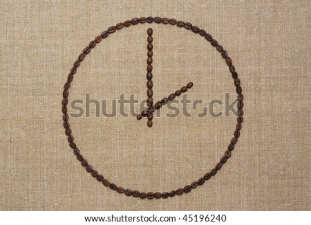 Clock made of fried coffee beans on grunge canvas. Coffee time concept.