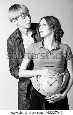 clock. Man is embracing stomach of a pregnant woman on gray background with painted watch - stock photo