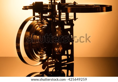 Clock mechanism on gold background. Focus on the central gears. High resolution. - stock photo