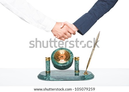 clock on a table and handshake on white background - stock photo