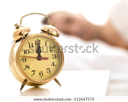 Clock on a table close up, man sleeping in the back - stock photo