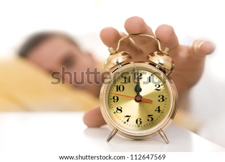 Clock on a table close up, man waking up - stock photo