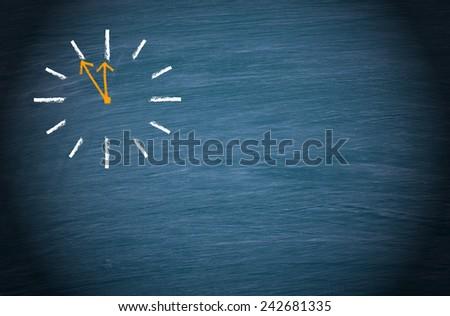Clock on blue chalkboard background - stock photo