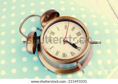 Clock on blue polka dot pillow, close-up - stock photo