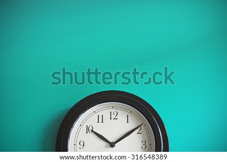 Clock on mint green wall background. Vintage effect. Concept of Time. - stock photo