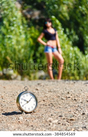 clock on the stone road and blurred girl at sunny day. it's time to travel