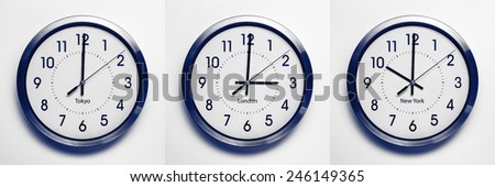 clock on the wall of time zones for trading around the world set at 3PM london GMT time. image is black and white with a blue tint - stock photo