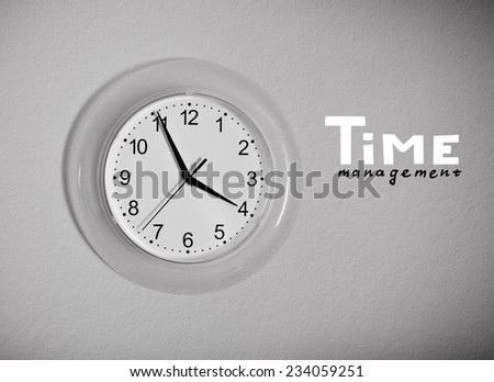 "Clock on the wall with ""Time management"" lettering, black and white photo - stock photo"