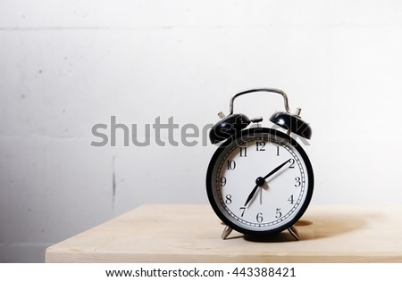 Clock on the wooden table on white background in the room - stock photo