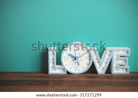 Clock on wooden table front mint green background. Vintage effect. - stock photo