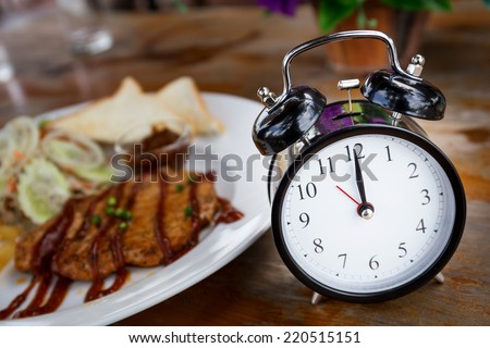 Clock on Wooden Table with steak on background, Lunch Time Concept - stock photo