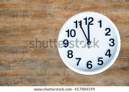 Clock show 5 minute to 12 am or pm on wood background with copy space. clipping path in picture. - stock photo
