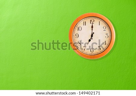 Clock showing 7:00 o'clock on a green wall