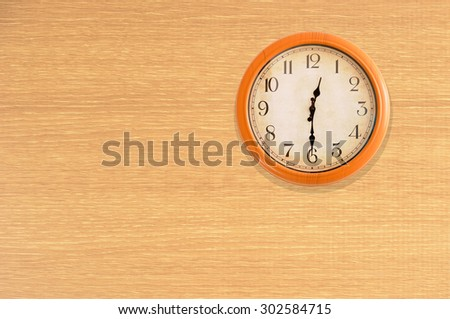 Clock showing 12:30 o'clock on a wooden wall - stock photo