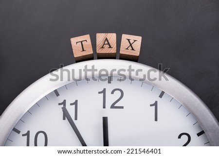 Clock showing tax time on black background