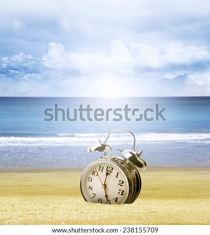 Clock stuck in sand at beach, bright sky behind - stock photo