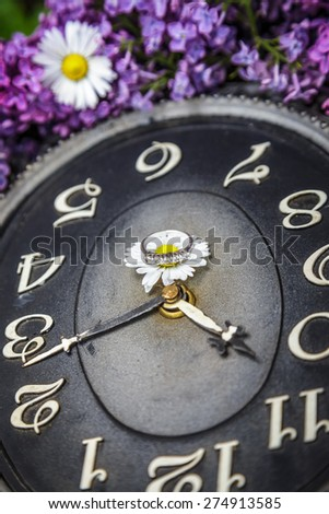 Clock surrounded by spring flowers with a ring in the middle.  Shallow depth of field with selective focus on the ring - stock photo