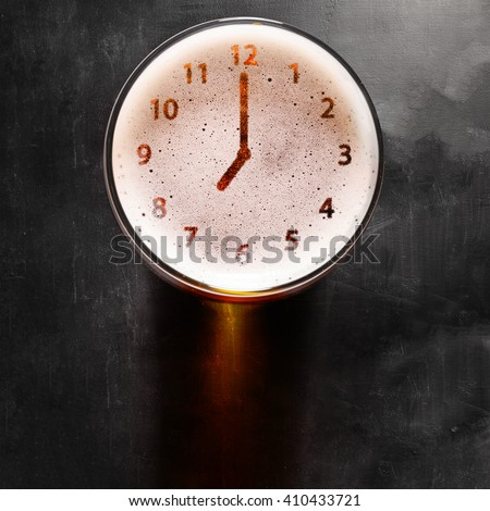 clock symbol on foam in beer glass on black table, view from above
