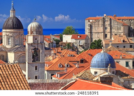 Clock tower and church domes dominate roof tops inside Dubrovnik old town, Croatia - stock photo