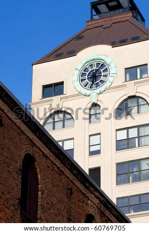 Clock tower in Dumbo with old brick building in front and beautiful clear blue sky