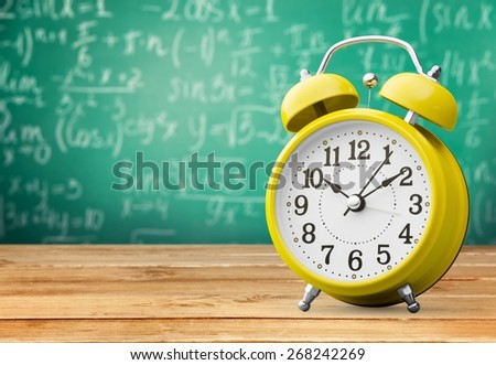 Clock. Vintage background with retro alarm clock on table - stock photo