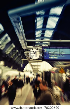 Clock watch in modern train station (Grand Central Station). Frankfurt am Main, Germany. Selected focus on clock. Peoples are blurred to show dynamic movements - stock photo