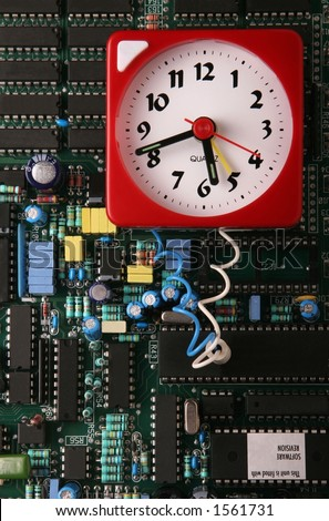 Clock 'wired' to a circuit board - stock photo