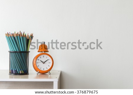 Clock with pen on white floor with walls - stock photo