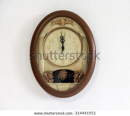 Clock with pendulum hanging at the white wall showing twelve o'clock. Decorative wall clock shows noon. Midnight time. Clock hanging on the wall showing midnight. Clock on the wall showing 12 hours.  - stock photo