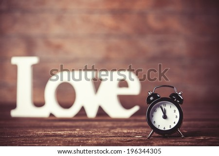 Clock with word love on wooden table. - stock photo