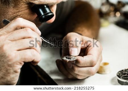 Clockmaker repairing wrist watch. Macro shot. - stock photo