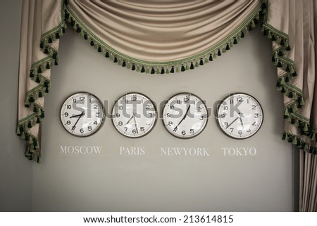 clocks on a wall with time zone of different country - stock photo