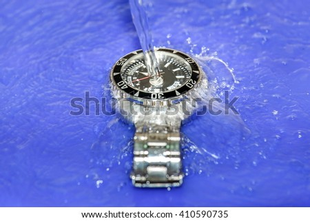 Clocks, watches, waterproof,metal wristwatch is falling and splashing into clear water - stock photo