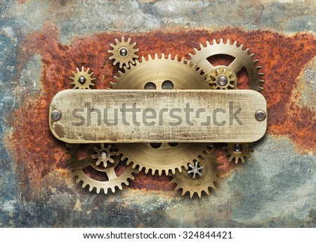 Clockwork mechanism on rusty background made of metal gears and brass plate. - stock photo