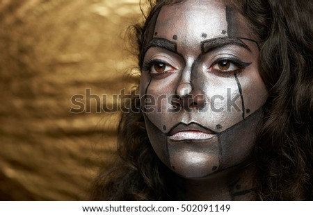 clode up of cyborg women face on golden background