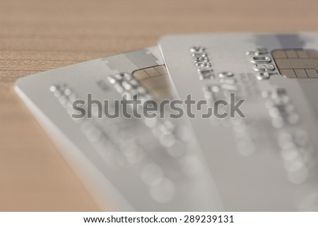 Cloesup view of two silver credit cards on a wooden table - stock photo