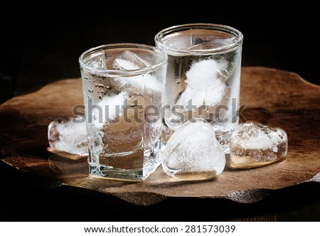 Clold fresh water with ice in a glass on a dark background in vintage style, selective focus - stock photo