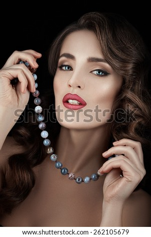 Close Beauty portrait of young brunette woman with make-up. In the hands of beads. Curly hair. - stock photo