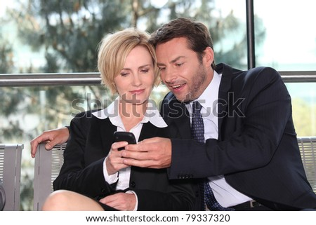 Close business colleagues looking at phone - stock photo