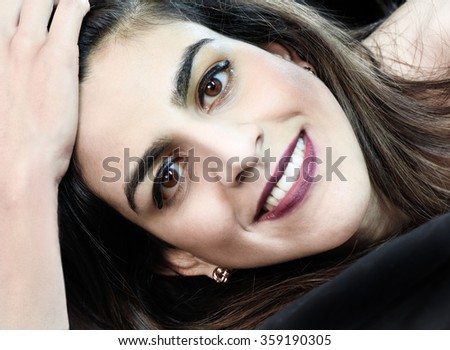 Close crop head shot of a happy and beautiful Indian girl looking straight to camera. Concept image for beauty, fashion, jewellry, dental, good health etc  - stock photo