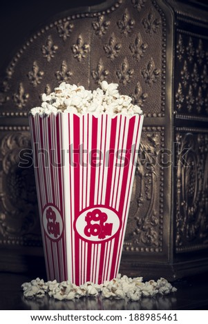 Close crop of a popcorn container filled with popcorn with a vintage national cash register in the background - stock photo