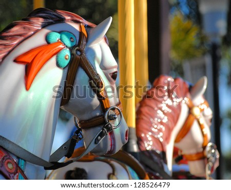 Close cropped detail of a carousel horse with the back of another in the background. The horse is painted white and has a turquoise and orange bridle decoration. It is lit with dappled sunshine - stock photo