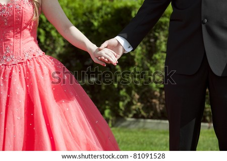 Close cropped outdoor photo of couple dressed in formal wear holding hands - stock photo