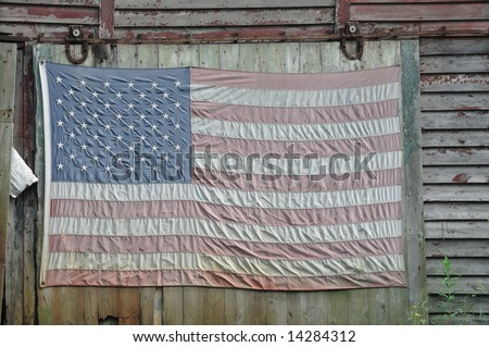 Close cropping of a faded American flag hanging from the side of an old red shack in Upstate New York.